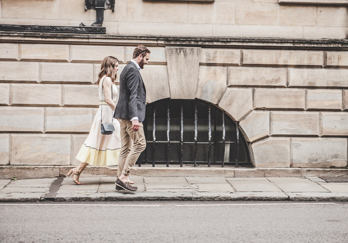 a couple holding hands and walking down the street