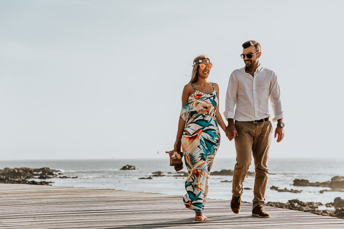 a couple holding hands and walking on a beach