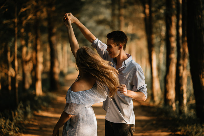 A playful couple pose in a forest