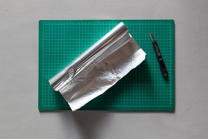 An overhead shot of a cutting mat, tin foil roll and Stanley knife - materials for how to make a lightbox for photography