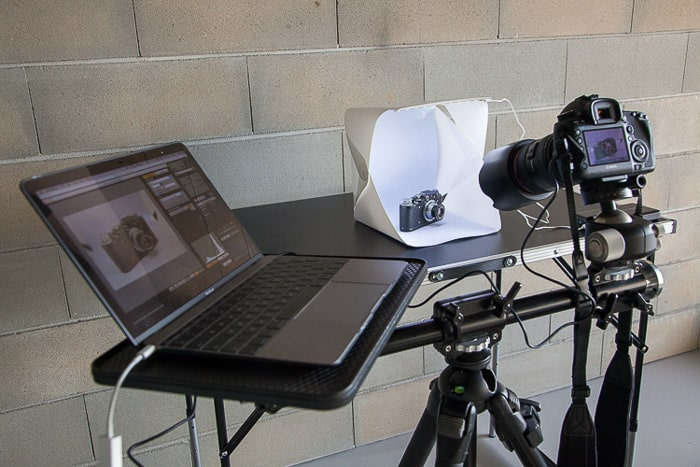 A diy photoshoot setup containing a laptop, diy light box, dslr camera on tripod