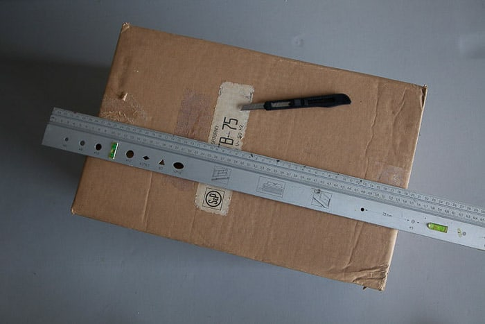 Overhead shot of a box, steel ruler and knife - tools you need to make a light box