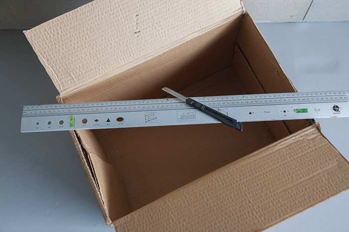 Overhead shot of an open cardboard box and other tools you need to make your own photography light box