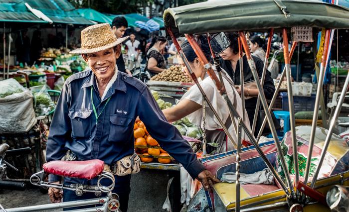 Una fotografía documental de viaje de un hombre asiático en un mercado callejero