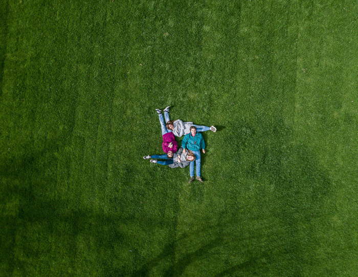An aerial view of a four person family posing on grass