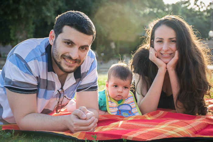 A couple posing with their baby son outdoors for a family portrait