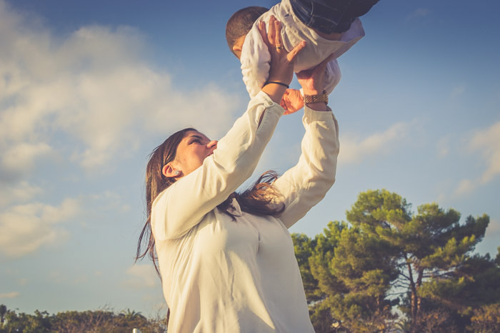 A mother playfully holding her child in the air