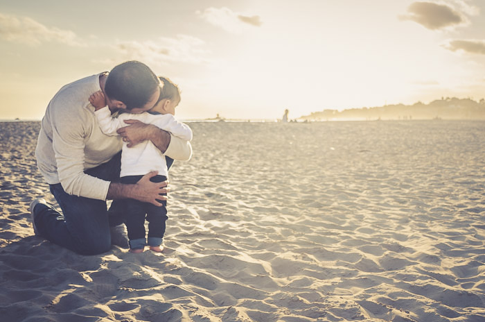 A father hugging his small son on the beach