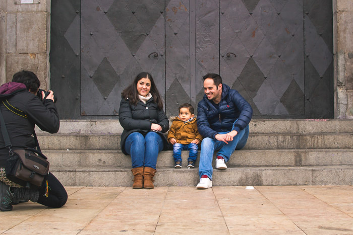 A couple and small child posing for a family portrait shoot on stone steps