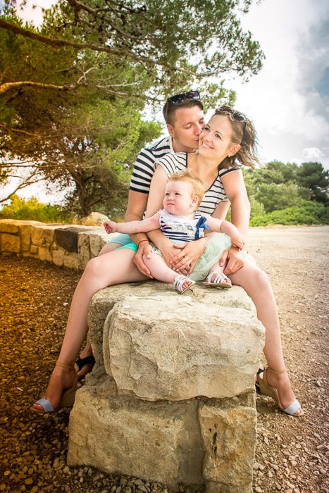 A couple and small child posing for a family portrait shoot by a stone wall