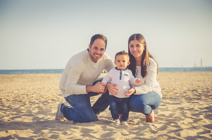 A couple posing with their baby son on the beach