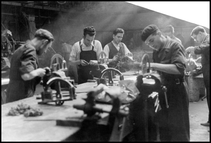Black and white photo of men at work in a factory by Gerda Taro
