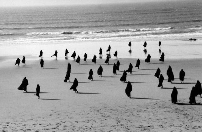 A group of people on a beach by Shirin Neshat