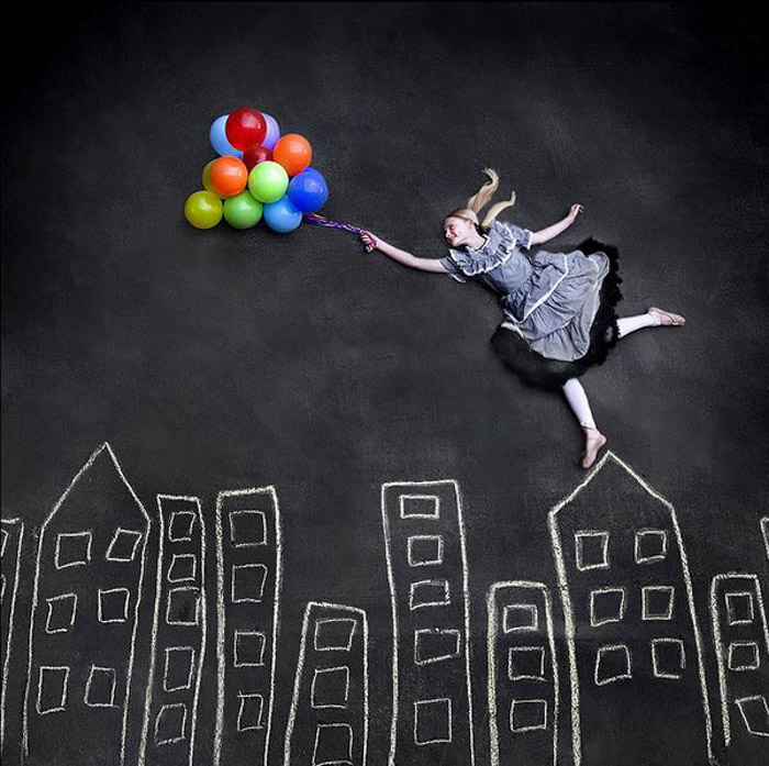 A woman holding balloons in an aerial photograph to show fine art photography possibilities