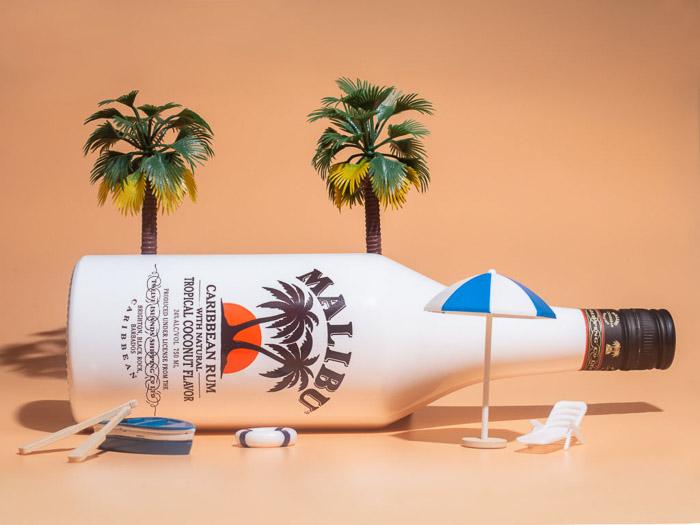A product photo of a Malibu bottle on a tiny beach scene