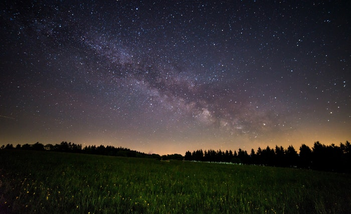 A landscape photo at night with the milky way