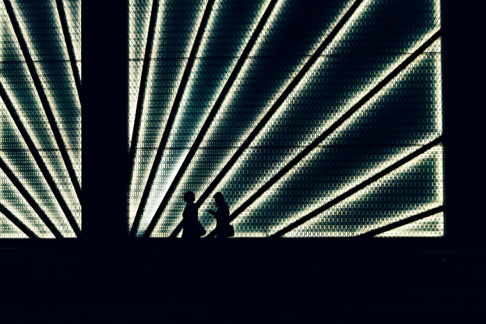 the silhouettes of people walking passed a lighted structure