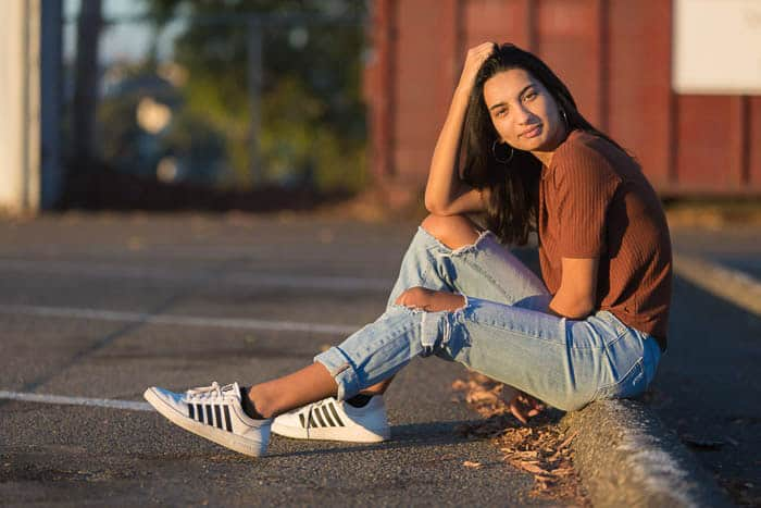 Casual portrait of a girl sitting on a pavement