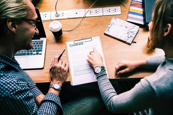 Un hombre y una mujer negociando un contrato de fotografía en una oficina en casa