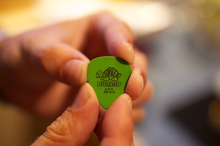 Close up of a person holding a green guitar plectrum