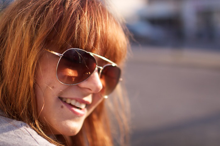 A portrait of a female model posing outdoors, shot with shallow depth of field