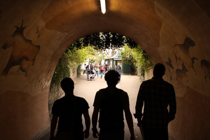 The silhouette of three people walking through a tunnel