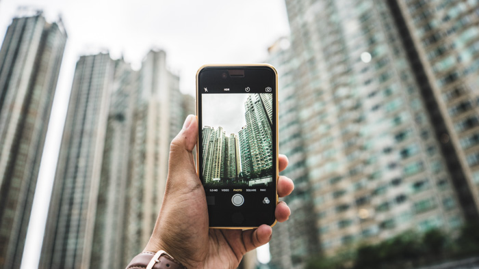 A person taking a photo of skyscrapers with a smartphone