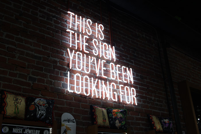 A neon sign saying 'This is the sign you've been looking for' on a brick wall