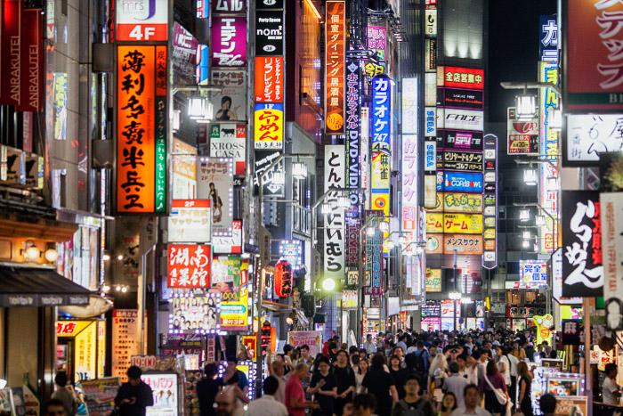 Uma imagem de fotografia de rua com outdoors de néon filmados em Tóquio à noite