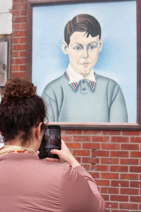 Fotografia de rua de uma mulher tirando fotos de arte de rua