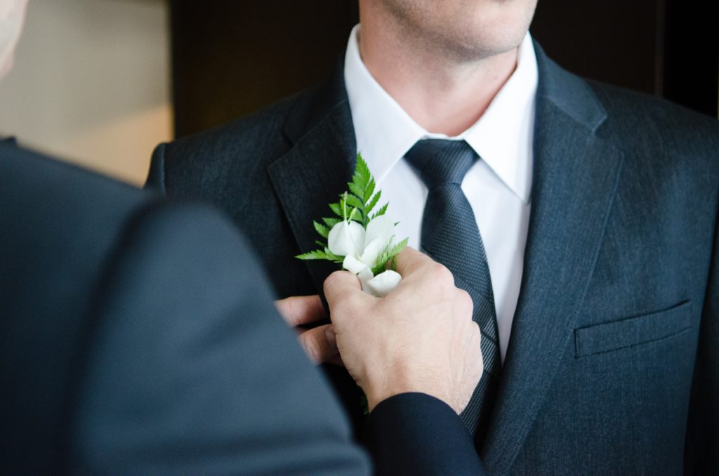A wedding portrait of a person pinning flowers on the grooms lapel