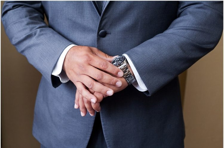 man in a navy suit looking at his watch