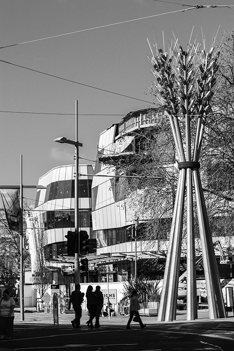 Black and white photo of a New Zealand street scene including the sculpture 'Flour Power' by Regan Gentry, buildings and people. Architecture Photography.