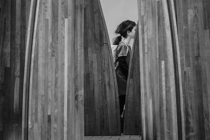 Black and white photo of a little girl framed by the artwork 'Tree Houses for Swamp Dwellers', Julia Morison, 2013. Christchurch, New Zealand. Architecture Photography.