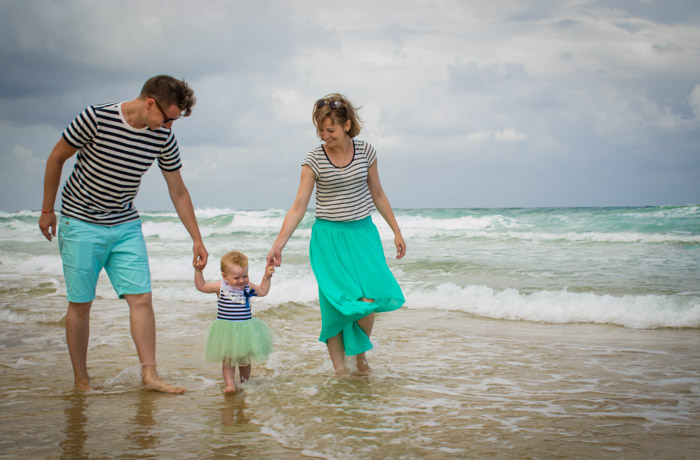family of three walking through waves on a beach