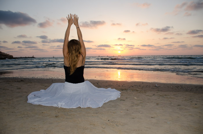 A photo of a girl sitting on the beach at sunset with her arms outstretched. Using flash for beach photography