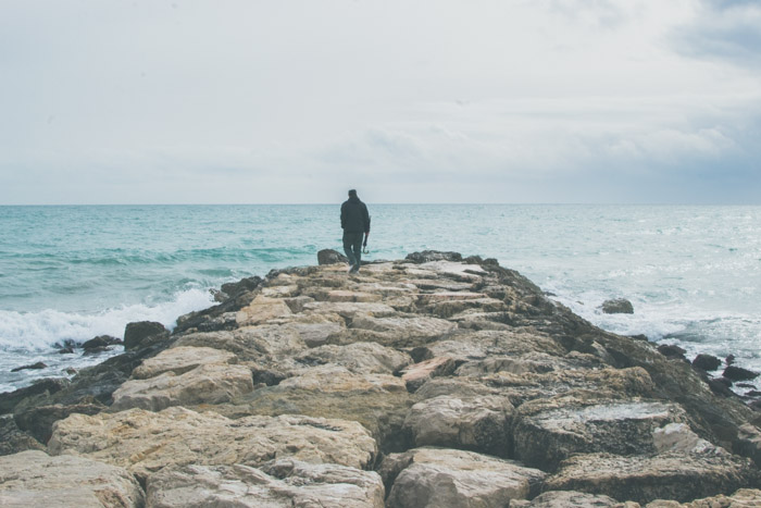 A lonely figure walking on a pier surrounded by the sea and the sky
