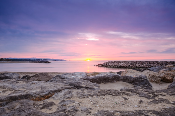 A beautiful beach landscape at sunset, with rocks in the foreground and a pink sky in the background