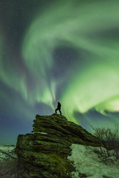 Photo of a person standing on a rock against the aurora borealis