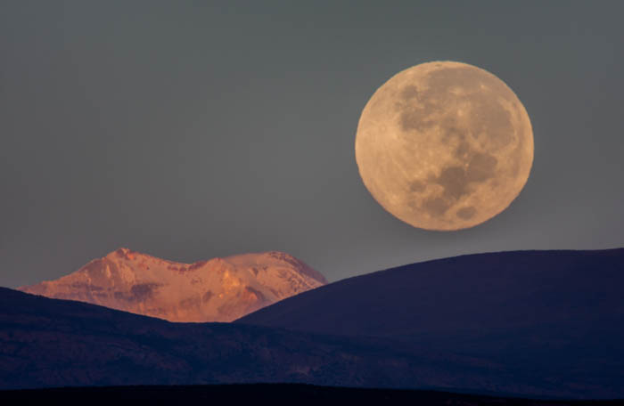 Photo of a large moon rising over the Andes mountain