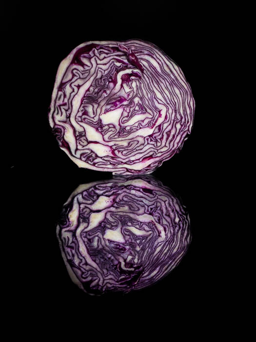 A half cabbage in front of a black background with its reflection