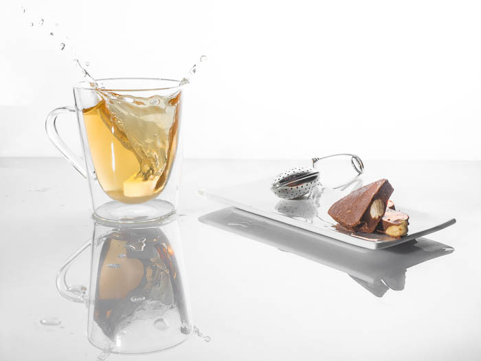 A minimalist food photo of a splashing cup of tea beside chocolates