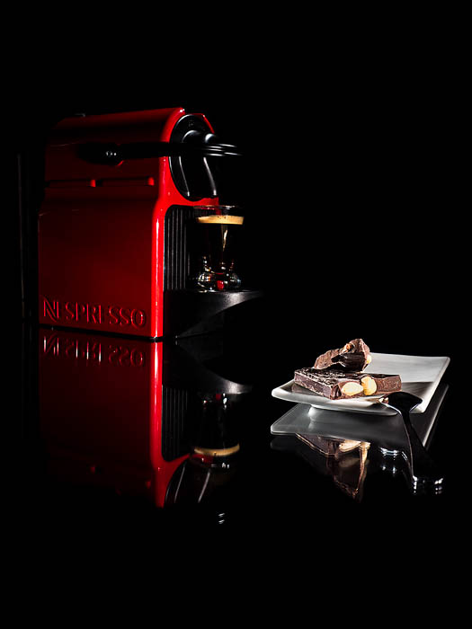 A commercial style photo of a Nespresso coffee machine beside a small plate of chocolates