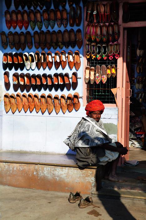 um vendedor de rua sentado ao lado de sua barraca