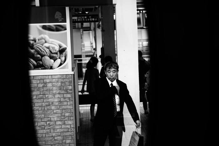 black and white pictures of a man in a suit walking on the street