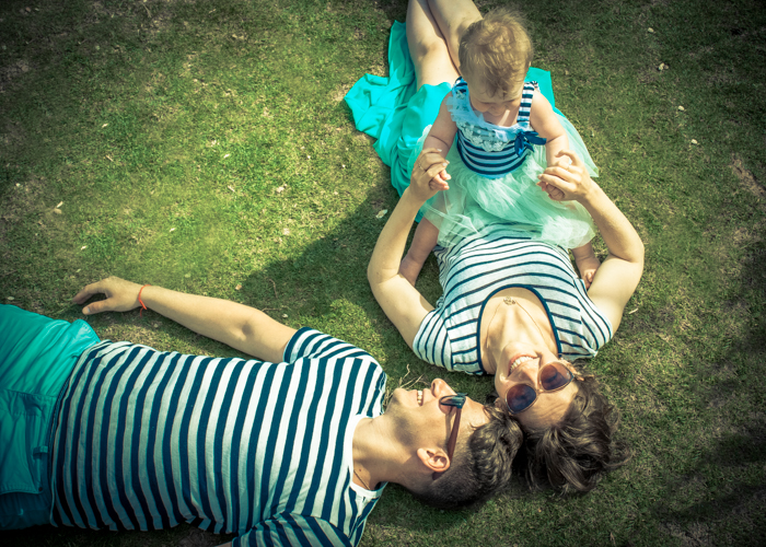 A shot of mom, dad and the little baby lying on grass