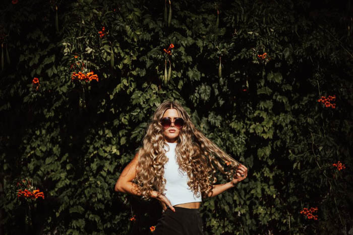 A fashion model posing in front of a bush - fashion photography composition