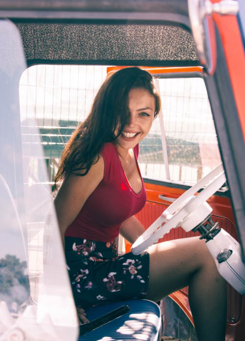 A female photography model sitting in the drivers seat of a vehicle - fashion photography composition