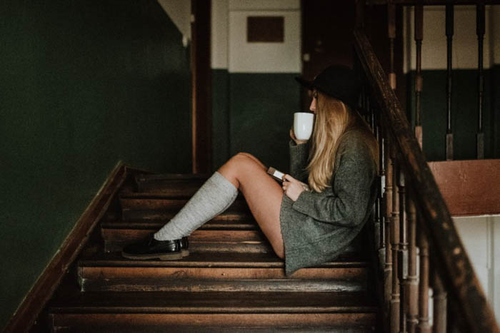 A female photography model sitting on a wooden staircase - fashion photography composition