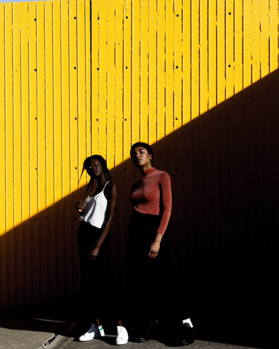Two female model posing outdoors against a yellow wall - fashion photography composition